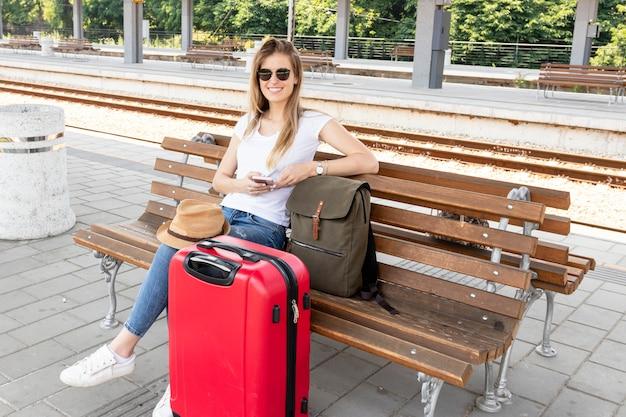Feliz viajero sonriendo en la estación de tren