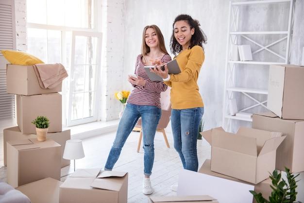 Feliz vida universitaria. estudiantes de sexo femenino alegres que revisan la lista de sus pertenencias en el cuaderno, habiéndose mudado a un nuevo apartamento compartido