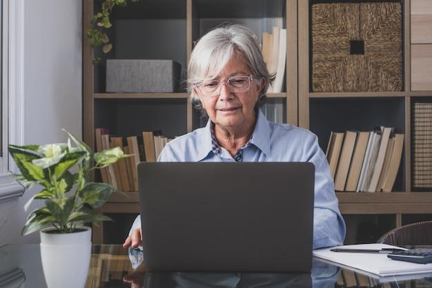Feliz vieja empresaria caucásica sonriendo trabajando en línea viendo podcast de seminarios web en la computadora portátil y el aprendizaje de conferencias telefónicas de cursos de educación hacer notas sentarse en el escritorio de trabajo, concepto de elearning