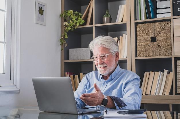 Feliz viejo hombre de negocios caucásico sonriendo trabajando en línea viendo podcast de seminarios web en la computadora portátil y el aprendizaje de conferencias telefónicas del curso de educación hacer notas sentarse en el escritorio de trabajo, concepto de elearning