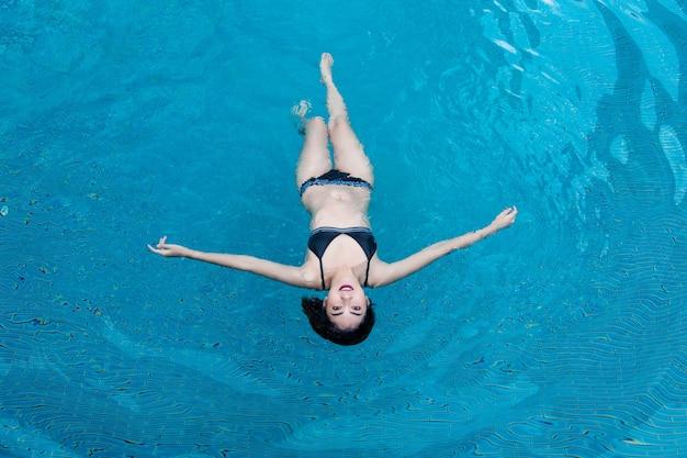 Feliz vocación mujer asiática relajarse en la piscina de agua