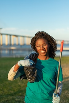 Feliz voluntario afroamericano posando en el parque de la ciudad