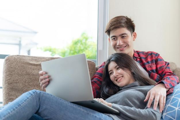 Felizmente joven y bella mujer y hombre guapo usando la computadora portátil en el sofá en el dormitorio en casa