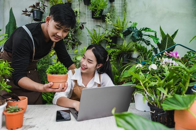Felizmente, la pareja de jardineros usa una computadora portátil mientras que el tutorial en línea sobre planes en macetas en el taller juntos