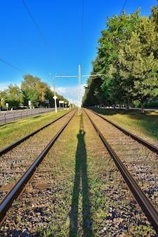 Ferrocarril en las vías del tranvía de la luz del sol brillante