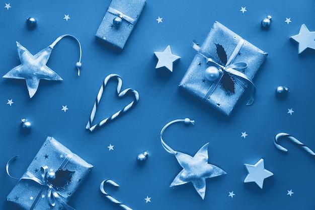 Festiva navidad monocromática rosa con cajas de regalo, bastones de caramelo a rayas, baratijas y estrellas decorativas, diseño plano creativo geométrico.