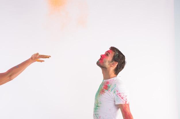 Festival de holi, amistad - jóvenes jugando con colores en el festival de holi sobre superficie blanca