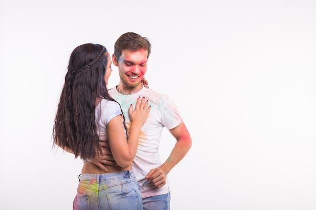Festival de holi, danza social, amistad: jóvenes jugando con colores y bailando bachata o kizomba en el festival de holi en superficie blanca con espacio de copia