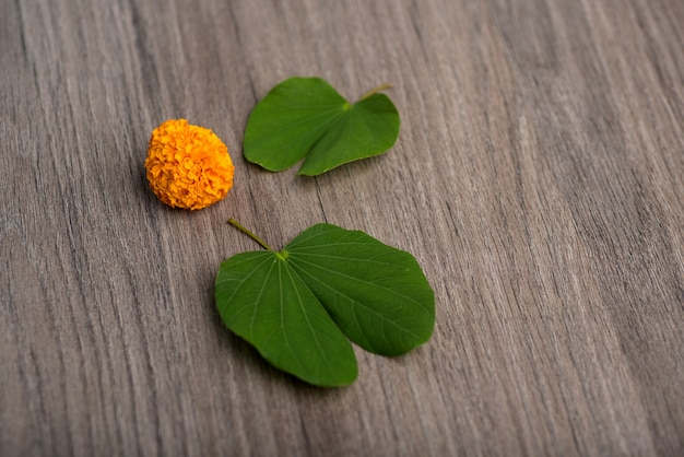 Festival indio dussehra, mostrando hojas de oro (bauhinia racemosa) y flores de caléndula sobre un fondo de madera.