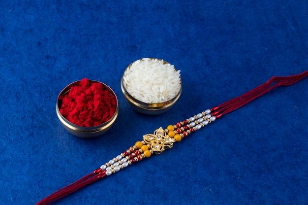 Festival indio: raksha bandhan con un elegante rakhi, rice grains y kumkum. una pulsera tradicional india que es un símbolo de amor entre hermanos y hermanas.