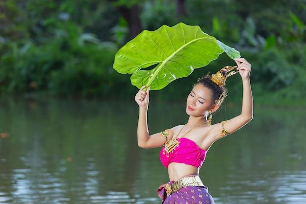 Festival de loy krathong. mujer en traje tradicional tailandés sosteniendo hoja de plátano
