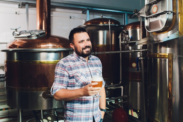 Festival de la oktoberfest. degustación de cerveza fresca elaborada. cervecero sostiene vidrio con cerveza artesanal. concepto de cervecería. hombre con cerveza de taza. alcohol. cervecero masculino sostiene el vaso con cerveza. oktober fest. barman. cervecero.
