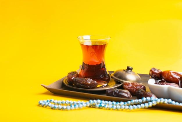 Festival ramadan kareem, fechas en un tazón de madera con una taza de té negro y rosario