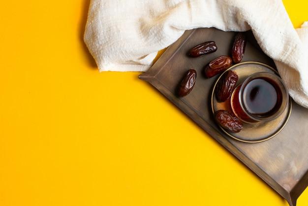 Festival de ramadan kareem, fechas en un tazón con una taza de té negro
