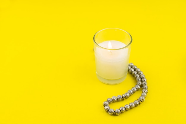 Festival ramadán kareem. vela y rosario sobre fondo amarillo. feliz ramadán hoilday. copia espacio