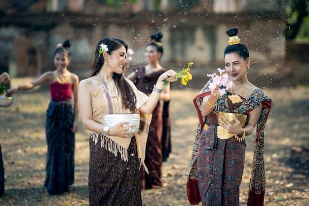 Festival songkran muchas mujeres jóvenes con trajes nacionales tailandeses están salpicando agua el día de songkran.