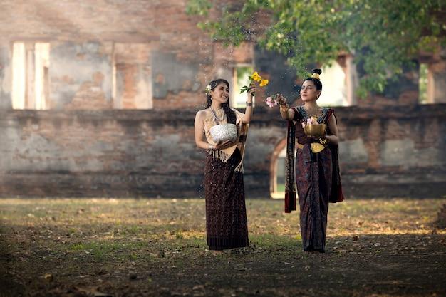 Festival de songkran. la niña en traje nacional tailandés está salpicando agua el día de songkran.