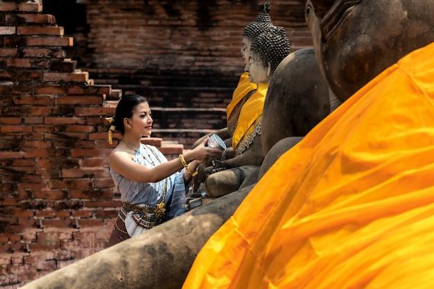 Festival de thaland mujer de asia que lleva el traje tailandés tradicional que descansa a buda que se baña en festival del agua del día de songkran en tailandia.