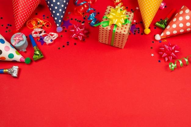 Festivas estrellas doradas y púrpuras de confeti y un regalo, gorras de cumpleaños sobre un fondo rojo.