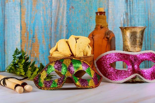 Festividad judía de purim con galletas hamantaschen, máscara de carnaval y matraca