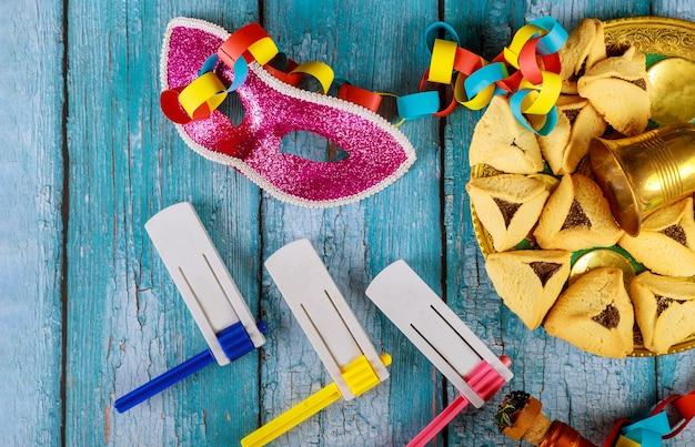 Festividad judía de purim con galletas hamantaschen orejas de hamans, máscara de carnaval y pergamino kippa, cuerno, sobre fondo rústico