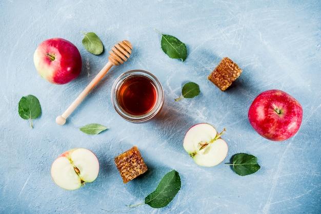 Festividad judía rosh hashaná o concepto de día de fiesta de manzana, con manzanas rojas, hojas de manzana y miel en frasco, fondo azul claro