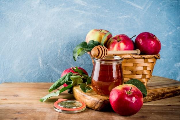 Festividad judía rosh hashaná o concepto de fiesta de manzana, con manzanas rojas, hojas de manzana y miel en frasco