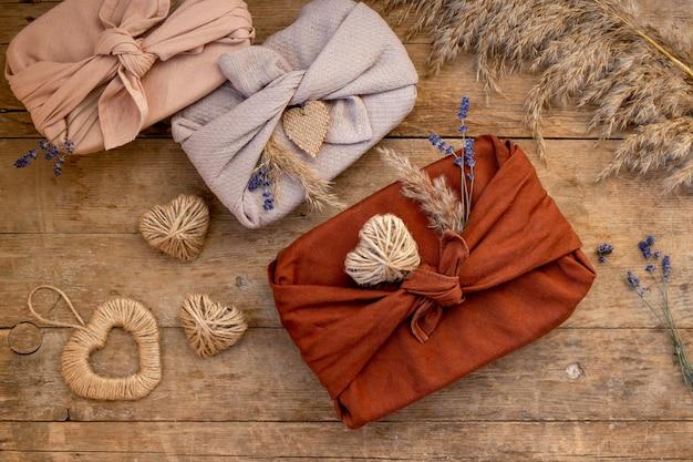 Festivo llanamente de regalos empaquetados en estilo furoshiki sobre mesa de madera. concepto de san valentín sin residuos