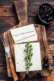 Feta de queso fresco con tomillo y aceitunas. mesa de madera oscura. vista superior.