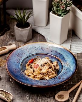 Fettuccine alfredo con parmesano rallado de champiñones y tomate cherry