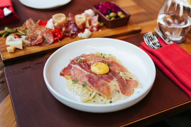 Fettuccine carbonara con jamón de parma y yema con pimienta negra. servido en plato blanco.