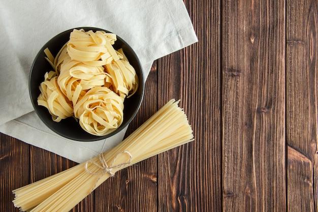 Fettuccine pasta con espagueti en un recipiente sobre fondo de madera y papel de cocina, plano.