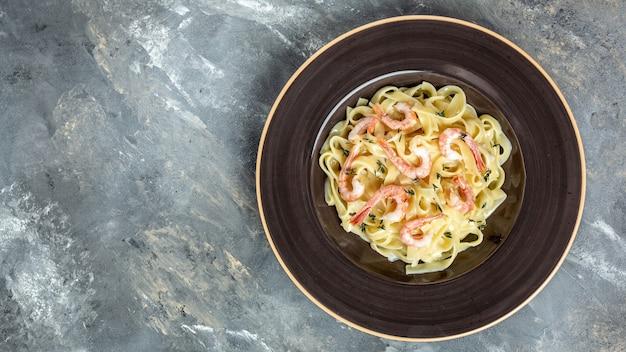 Fettuccine de pasta italiana con camarones a la plancha, salsa bechamel y tomillo, pasta fettuccine. comida italiana. formato de banner largo, vista superior.