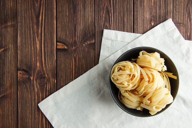 Fettuccine pasta en un recipiente sobre fondo de madera y toalla de cocina. aplanada