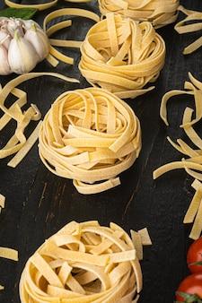 Fettuccine tagliatelle pasta ingredientes de comida italiana, sobre mesa de madera negra