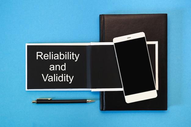 Fiabilidad y validez escritas en un cuaderno con páginas negras junto a un teléfono inteligente y un bolígrafo