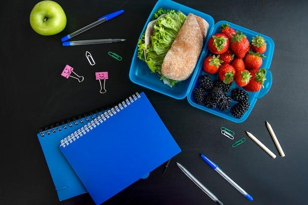 Fiambrera, cuadernos y papelería sobre mesa.