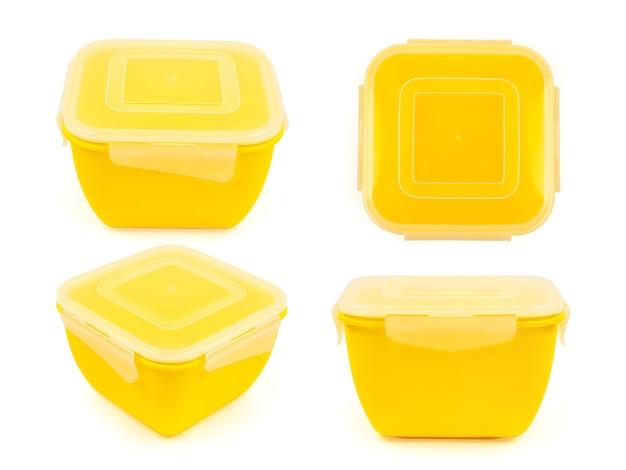 Fiambrera cuadrada de plástico amarillo en cuatro proyecciones aislado sobre fondo blanco.