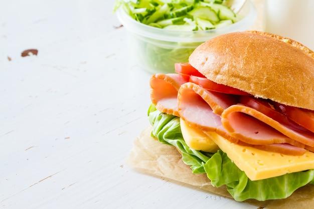 Fiambrera con ensalada de sandwich y friuts.