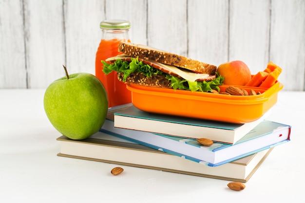 Fiambrera escolar con sandwich, frutas y frutos secos.