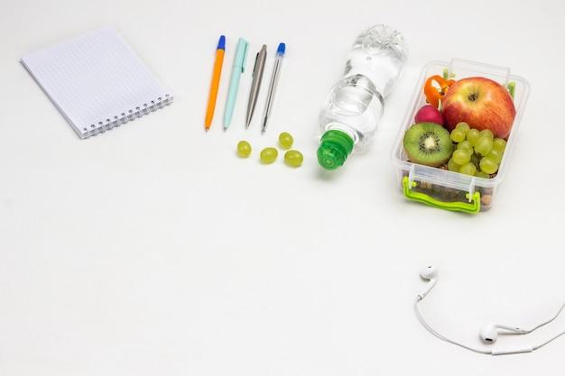 Fiambrera con frutas en la mesa. bloc de notas, bolígrafos, auriculares y botella de agua en blanco