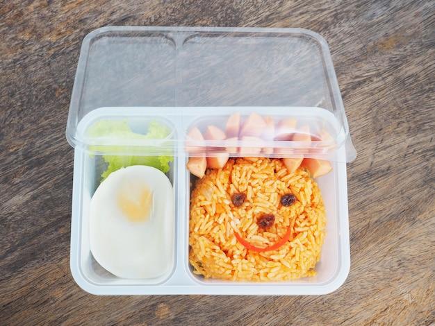 Fiambrera plástica para niños con cara divertida de arroz frito y huevo.