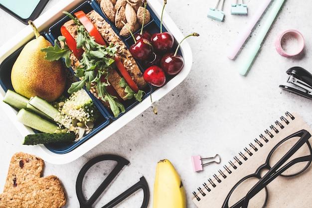 Fiambrera con sandwich, frutas, bocadillos, cuaderno, lápices y artículos escolares, vista superior.