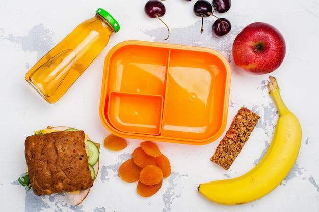 Fiambrera, sandwich y frutas.