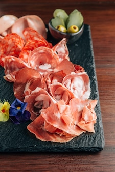 Fiambres en placa de piedra con jamón, tocino, salami y salchichas