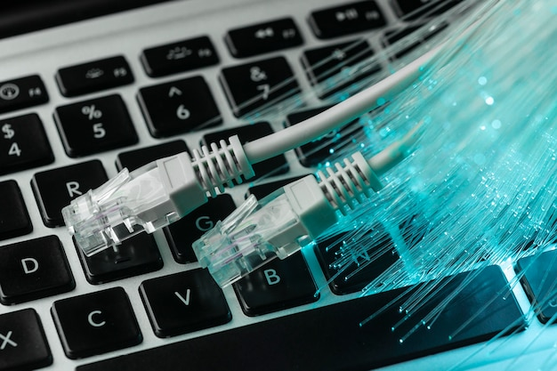 Fibra óptica azul con cables ethernet y portátil