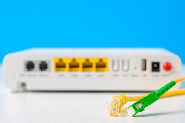 Fibra óptica y cables de red con enrutador inalámbrico de internet sobre un fondo azul