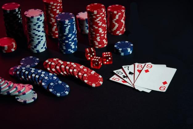 Fichas de casino y cartas sobre la superficie de la mesa negra. concepto de juego, fortuna, juego y entretenimiento - de cerca. poker en línea. copie el espacio. ideal para publicidad. naturaleza muerta