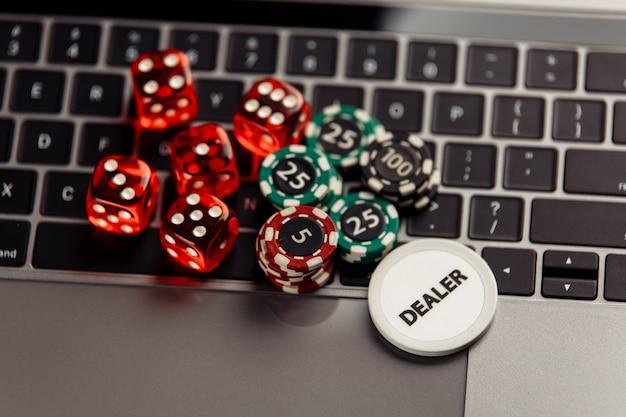 Fichas de juego y dados en el teclado del portátil