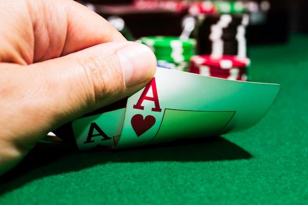 Fichas de póquer y as de picas y as de corazones sobre una alfombra verde